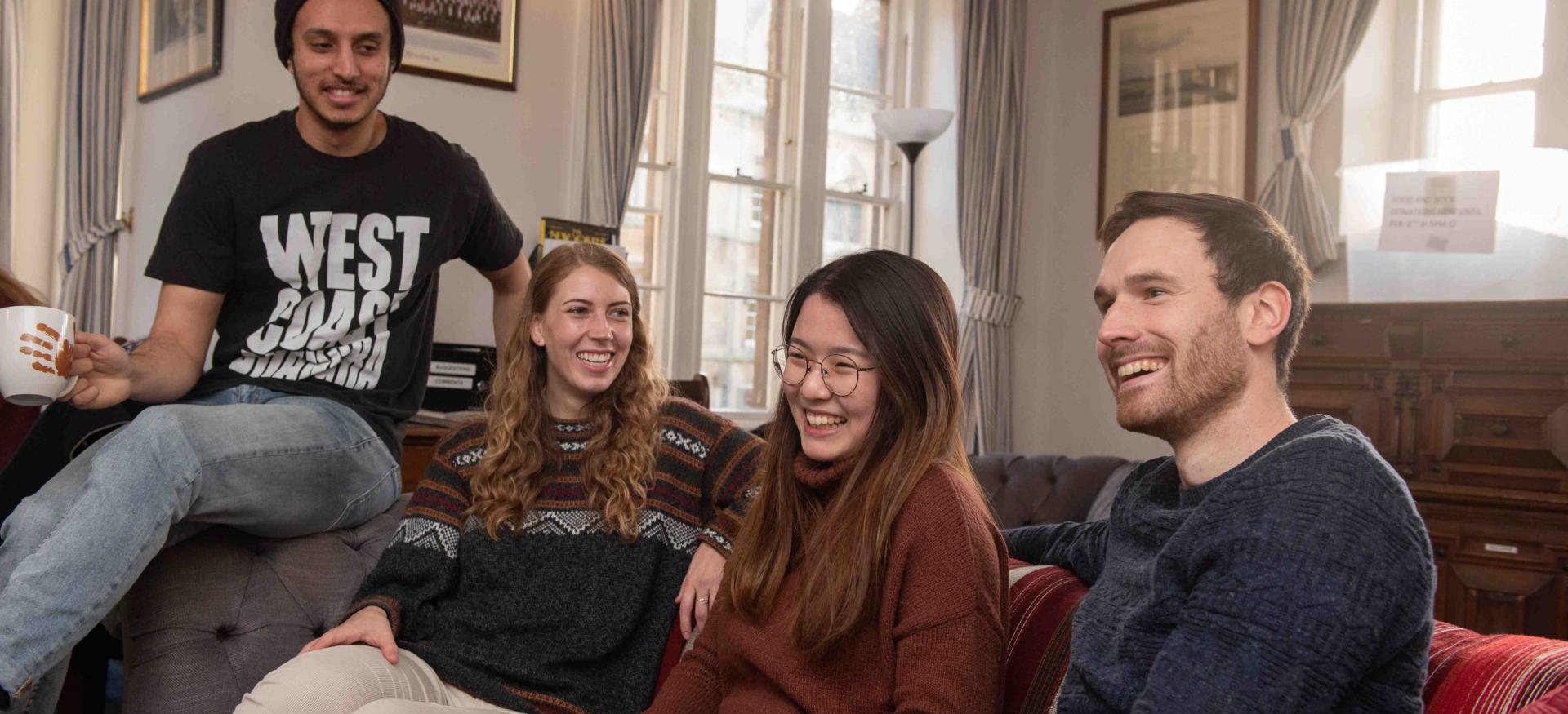 A group of four male and female postgraduate students sit on a couch laughing.