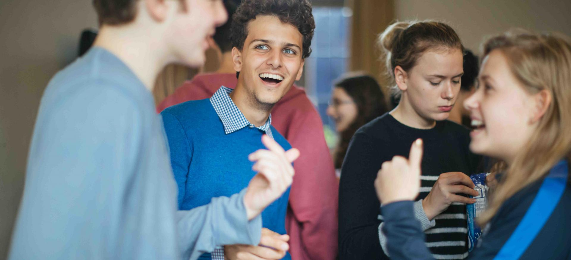 A group of students talk and laugh in the Trinity JCR; the image focuses on a male student laughing and looking at another student.