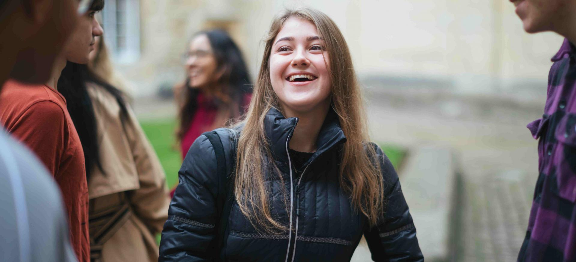 A female student smiles while talking to other students in Trinity College's Durham Quad.