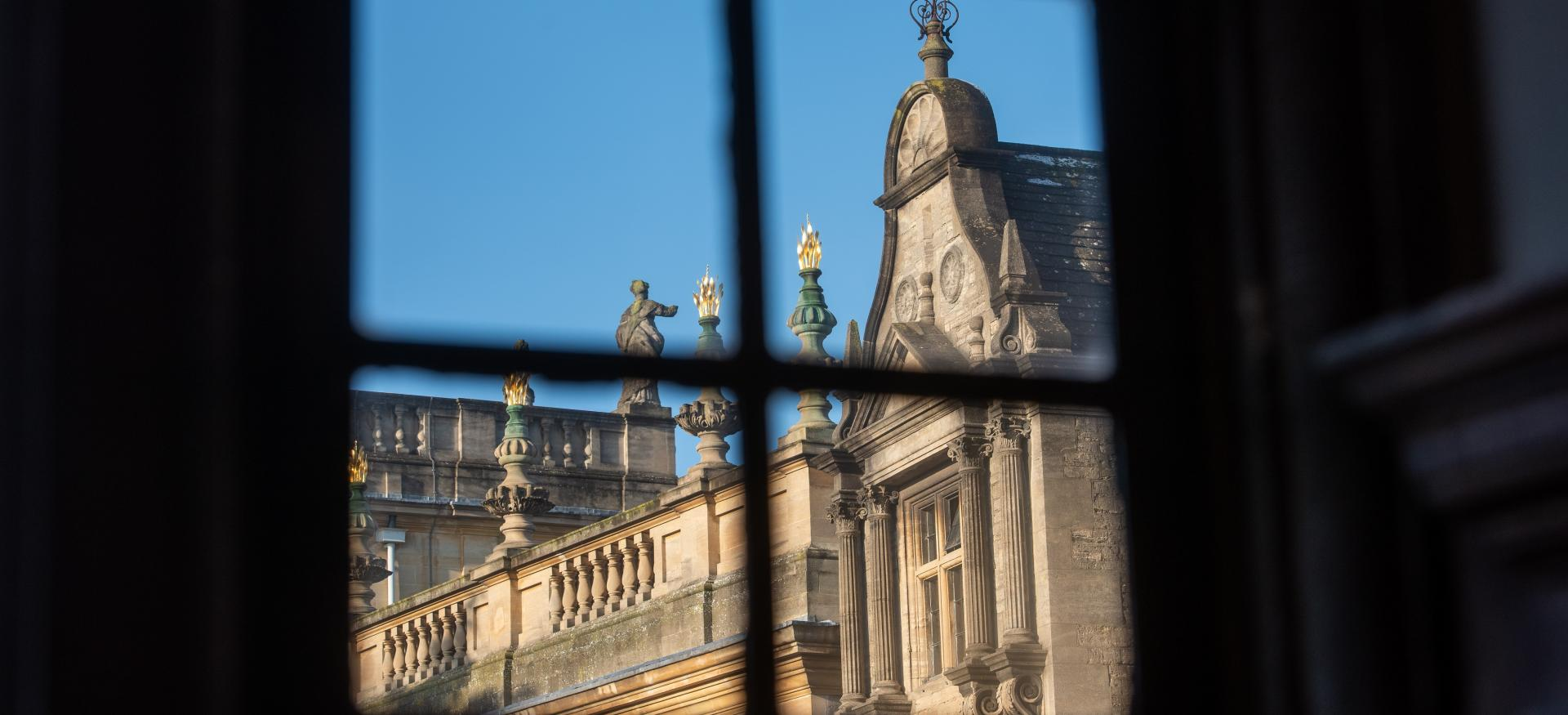 A view of the Trinity College chapel and president's lodgings through a window.