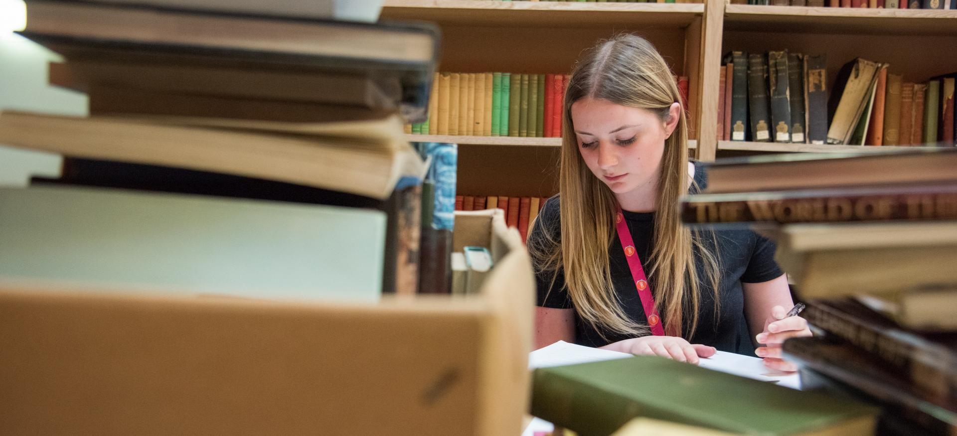 A student studies among a pile of books and folders with a bookshelf in the background.