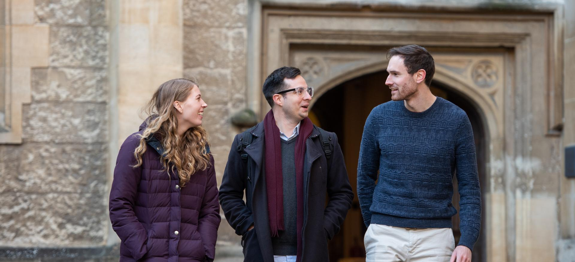 Three Trinity College postgraduates walk chatting to each other as they come out of the college dining hall.