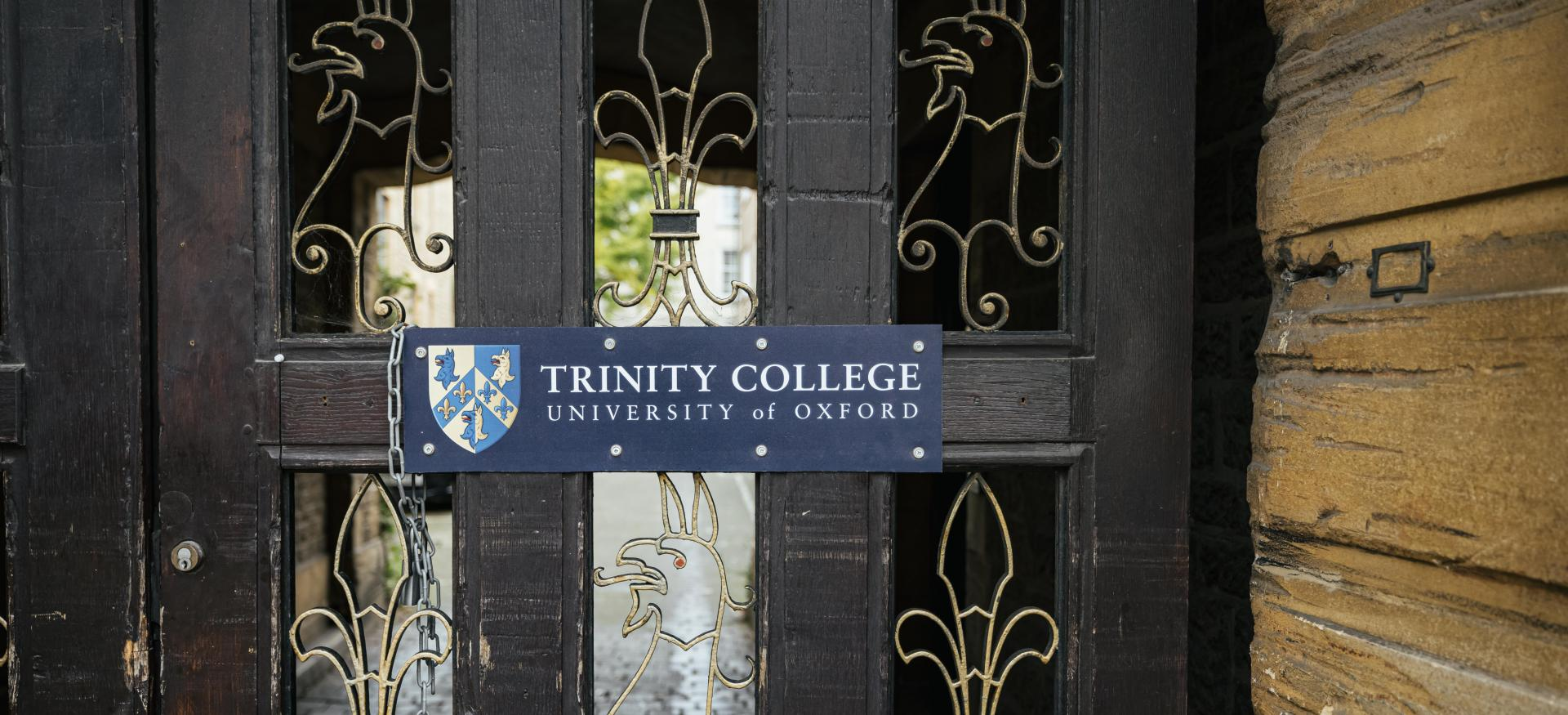 The side entrace to trinity College with ironwork in the shape of gryphons and a sign reading 'Trinity College Oxford'