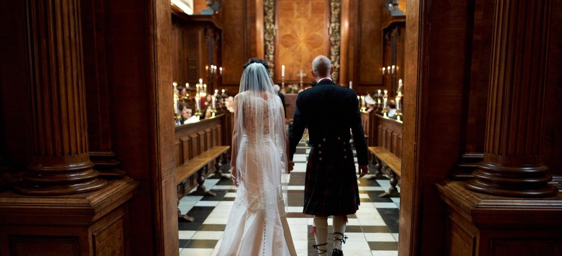 A bride and groom walk into the Trinity College chapel during a wedding service.
