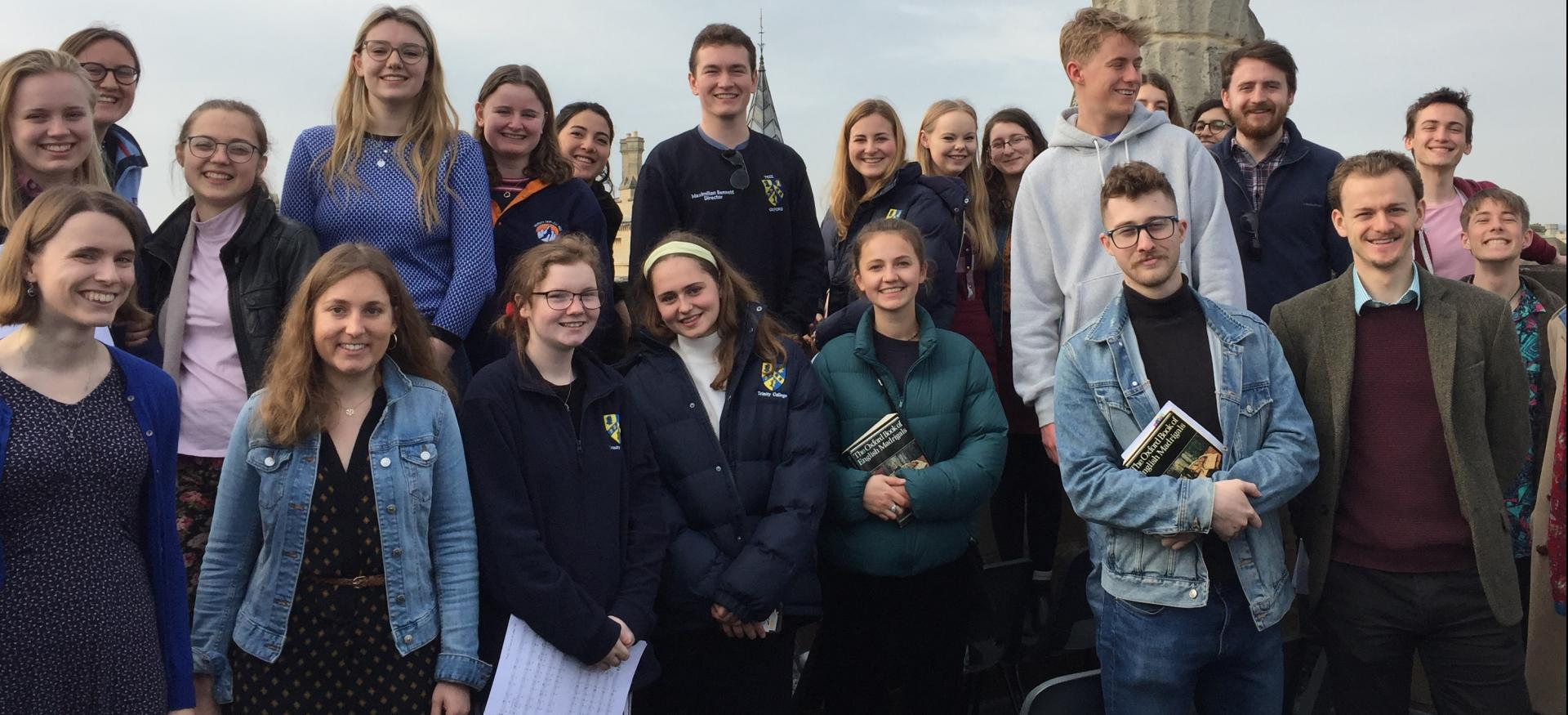 The Trinity College chapel choir stands on top of the chapel after singing for May morning