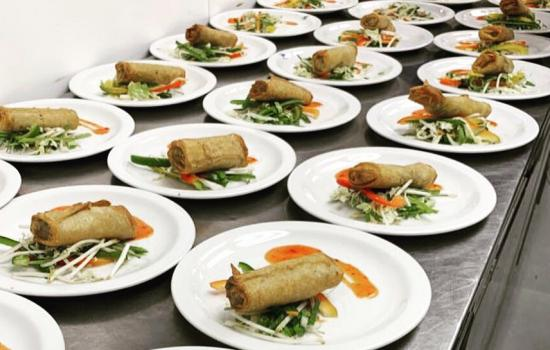 Three rows of plated food on a table ready to be served in the Trinity dining hall.