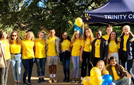 A group of Trinity College student ambassadors stands in front of a marquee at Open days.