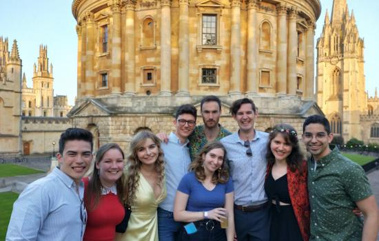 A group of Trinity postgraduates stands in front of the Radcliffe Camera in Oxford.