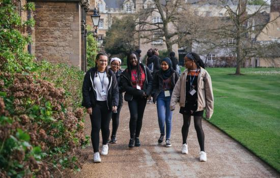 A group of secondary school students chats as they walk around Trinity College.