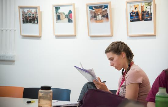 A female student writes in a notebook in a room with pictures hanging on the walls in the background.