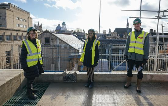 Trinity College's President, MCR President and JCR Presidents stand on the top of the Levine Building wearing hard hats and hi-vis jackets smiling. A partial view of the Oxford skyline is in the background.