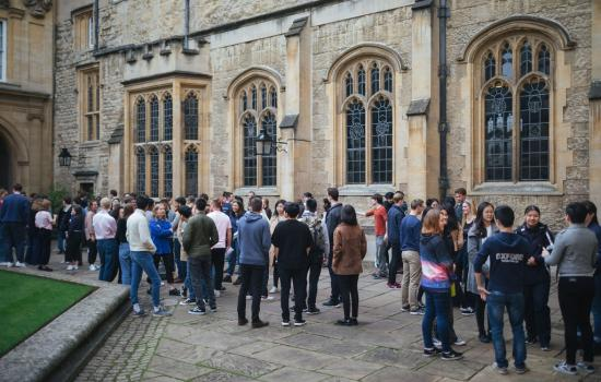 A large group of students stand talking outside the Trinity College dining hall.