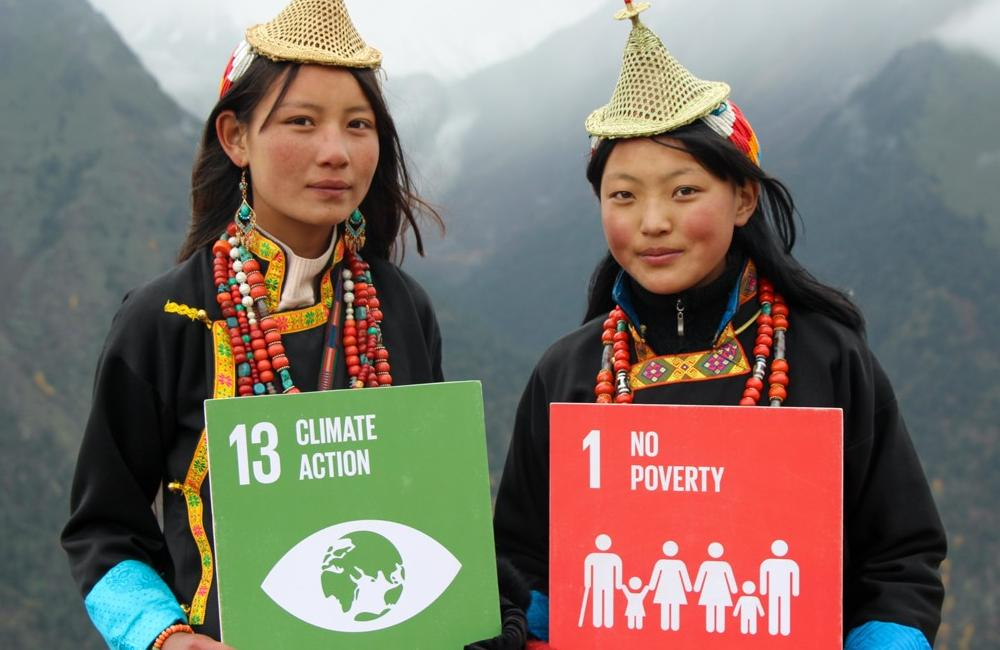 Two girls in Bhutan hold up signs saying 'climate action' and 'no poverty'.