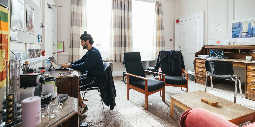 A male student studies in the common room of a second-year room set.