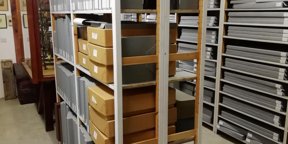 An image of the college archive storage area with shelving full of ledgers and boxes.