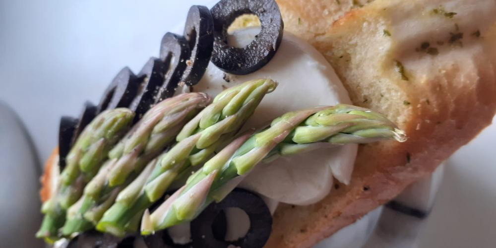 A bruschetta with olive and asparagus topping.