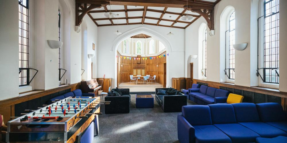 The common area of The Nunnery is shown with couches and table football.