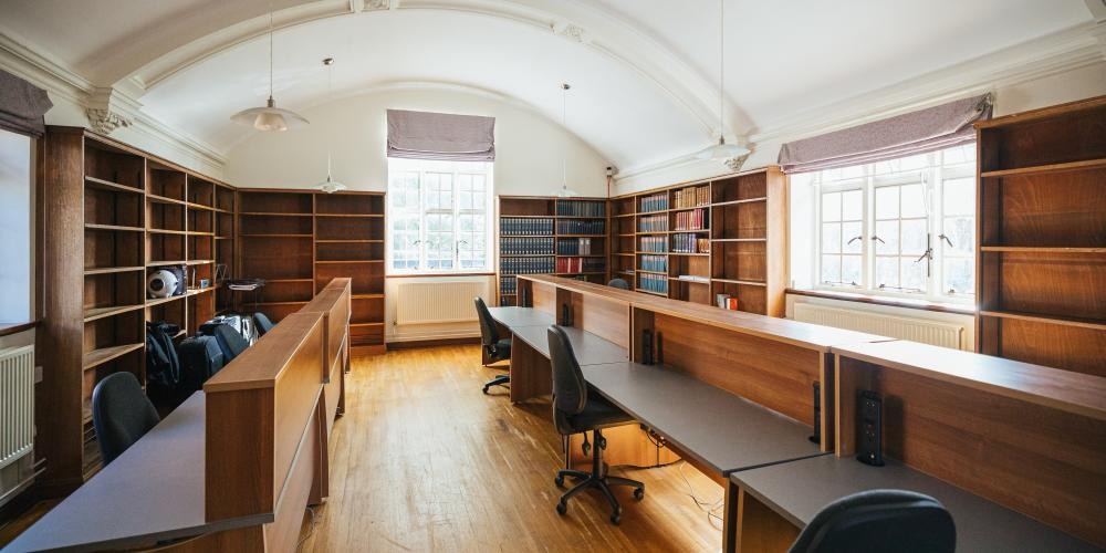 The study library in the Old Nunnery with empty desk spaces and light shining in the windows.