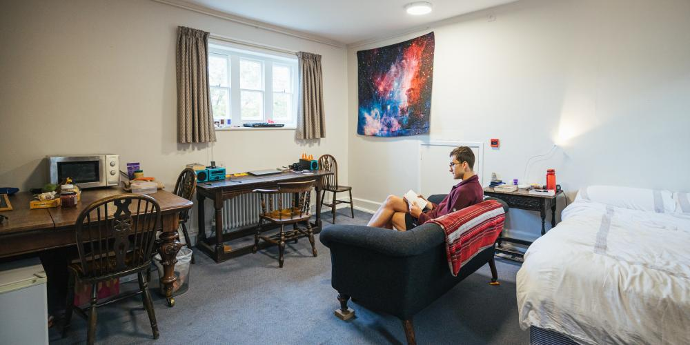 An student sits reading on the couch in a postgraduate room on Trinity's main site.